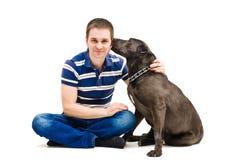 Jeune homme et son chien de lèchement Photos stock
