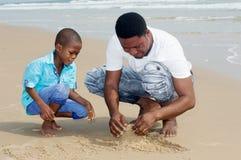 Jeune homme et son fils à la plage photos stock