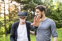 Jeune homme et son père supérieur avec des verres de VR dehors Photo libre de droits