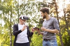 Jeune homme et son père supérieur avec des verres de VR dehors Images stock