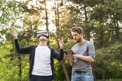 Jeune homme et son père supérieur avec des verres de VR dehors Images libres de droits