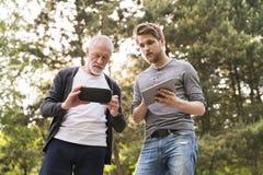 Jeune homme et son père supérieur avec des verres de VR dehors Photos libres de droits