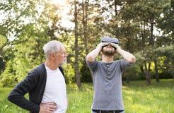 Jeune homme et son père supérieur avec des verres de VR dehors Image stock