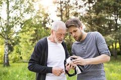 Jeune homme et son père supérieur avec des verres de VR dehors Photos stock