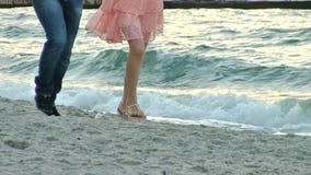 Jeune homme et une course de femme le long du rivage amoureux Au ralenti banque de vidéos