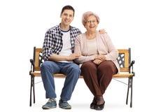 Jeune homme et une femme agée s'asseyant sur un banc Photographie stock libre de droits