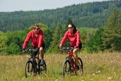 Jeune homme et vélo de montagne d'équitation de femme Photos stock
