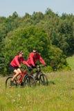 Jeune homme et vélos de montagne d'équitation de femme Images stock