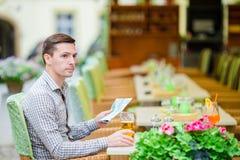 Jeune homme européen caucasien avec le citymap en café d'extérieur Le portrait du jeune touriste attirant dînent Photographie stock libre de droits