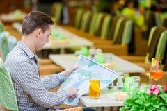 Jeune homme européen caucasien avec le citymap en café d'extérieur Portrait de jeune touriste attirant le temps de déjeuner Photo stock