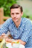 Jeune homme européen caucasien dans une chemise bleue en café d'extérieur Le portrait des jeunes attrayants dînent Image libre de droits