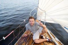 Jeune homme européen s'asseyant sur le yacht regardant la mer photos stock