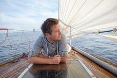 Jeune homme européen s'asseyant sur le yacht regardant la mer images stock