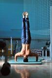 Jeune homme exécutant le handstand dans le studio de forme physique photographie stock libre de droits