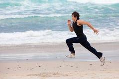 Jeune homme exécutant sur la plage photographie stock