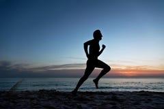 Jeune homme exécutant sur la plage Photo stock