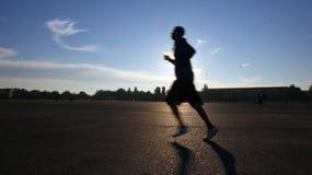 Jeune homme exécutant sur une piste au coucher du soleil Photos libres de droits