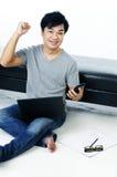 Jeune homme Excited s'asseyant sur l'étage avec l'ordinateur portatif Photographie stock