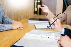 Jeune homme expliquant au sujet de son profil au sitt de directeurs commerciaux Image stock