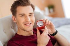 Jeune homme extrêmement heureux posant dans l'appareil-photo avec l'anneau de proposition Photos libres de droits