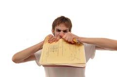 Jeune homme fâché déchirant les papiers de essai image stock