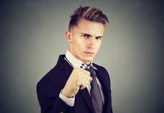 Jeune homme fâché d'affaires avec le poing fermé regardant l'appareil-photo images libres de droits