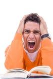 Jeune homme fâché et bouleversé dans le livre de lecture de chandail Photographie stock