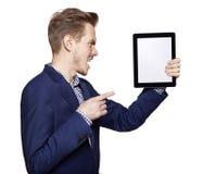 Jeune homme fâché se dirigeant à la tablette Image stock