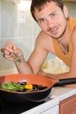 Jeune homme faisant cuire des fruits de mer. Photos libres de droits
