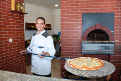 Jeune homme faisant cuire la pizza Photo libre de droits
