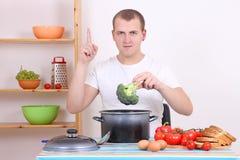 Jeune homme faisant cuire le brocoli dans la cuisine Image libre de droits