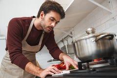 Jeune homme faisant cuire le dîner romantique à la maison lisant le plan rapproché de reçu Images stock