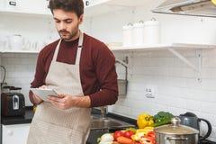 Jeune homme faisant cuire le dîner romantique à la maison passant en revue le comprimé numérique Photos stock