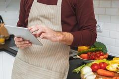 Jeune homme faisant cuire le dîner romantique à la maison passant en revue le plan rapproché numérique de comprimé Images stock