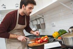Jeune homme faisant cuire le dîner romantique à la maison regardant le reçu Photo libre de droits