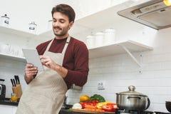 Jeune homme faisant cuire le dîner romantique à la maison utilisant le comprimé numérique Images stock