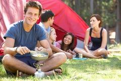 Jeune homme faisant cuire le petit déjeuner pour des amis des vacances de camping Image stock