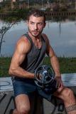Jeune homme faisant des boucles de biceps Image stock