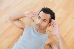 Jeune homme faisant des craquements abdominaux sur le plancher de parquet photographie stock libre de droits