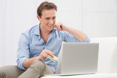 Jeune homme faisant des emplettes en ligne Image libre de droits