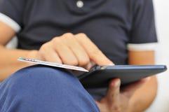 Jeune homme faisant des emplettes en ligne par l'intermédiaire d'une tablette Images libres de droits