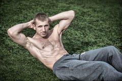 Jeune homme faisant des exercices pour des muscles abdominaux sur l'herbe verte photos libres de droits