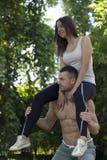 Jeune homme faisant des postures accroupies tout en tenant son amie sur son shoul Photographie stock libre de droits