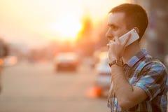 Jeune homme faisant l'appel avec le smartphone sur la rue ensoleillée photo stock