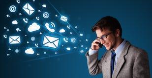 Jeune homme faisant l'appel téléphonique avec des graphismes de message Image stock