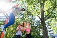 Jeune homme faisant l'exercice d'immersion pour le triceps sur les anneaux gymnastiques à la séance d'entraînement de rue Photos stock