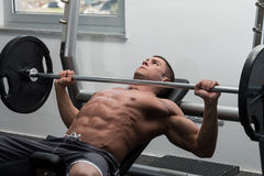 Jeune homme faisant l'exercice de banc à presse pour le coffre Photo stock