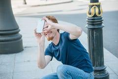 Jeune homme faisant la photo et la vidéo au téléphone Photo stock