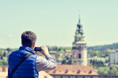 Jeune homme faisant la photo mobile d'appareil-photo du point de repère et de l'architecture de Cesky Krumlov images stock