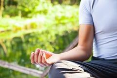 Jeune homme faisant la pose de lotus de yoga en parc photo stock